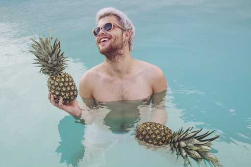 Smiling young man holding pineapples in swiming pool - RTBF00746