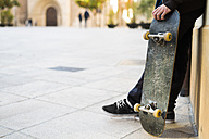 Young man with skateboard leaning against house front - KKAF00502
