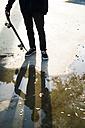 Skateboarder in a skatepark reflected in a puddle - KKAF00511