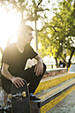 Young man sitting with skateboard in a skatepark - KKAF00514