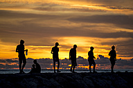 Indonesia, Bali, people at sunset time at ocean coastline - KNTF00745