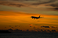 Indonesia, Bali, airplane in the sky and sunset over the ocean - KNTF00748