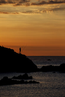 Spain, Costa Brava, Blanes, lone angler and Sa Palomera rock silhouette at sunrise by the Mediterranean Sea - ABOF00166