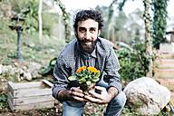 Smiling gardener holding a flower - JRFF01261