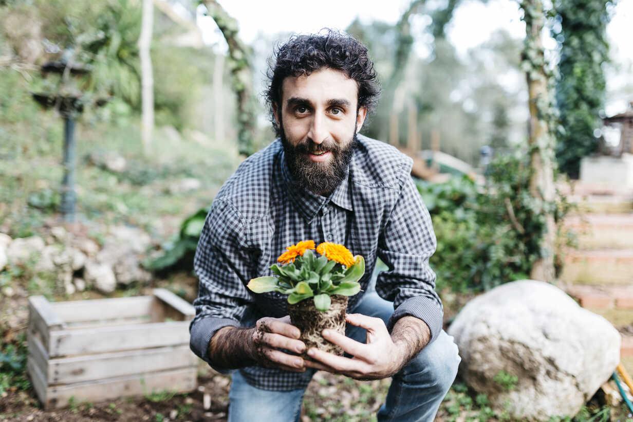 Smiling gardener holding a flower - JRFF01261 - Josep Rovirosa/Westend61
