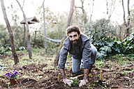 Man planting flowers in his garden - JRFF01267