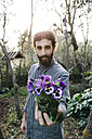Man holding a flower in garden - JRFF01270