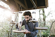 Man putting food for the birds in their feeders - JRFF01279