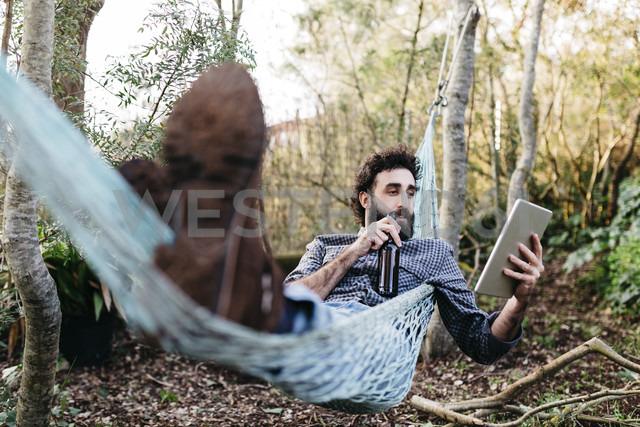 Man lying in hammock drinking beer and using tablet - JRFF01285
