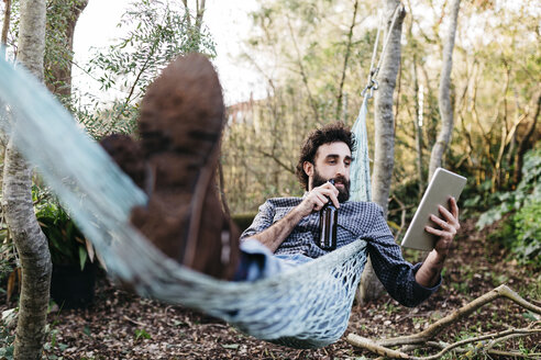 Man lying in hammock drinking beer and using tablet - JRFF01285