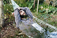 Man lying relaxed in hammock with a tablet - JRFF01288