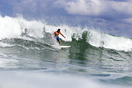 Indonesia, Bali, man surfing on a wave - KNTF00749