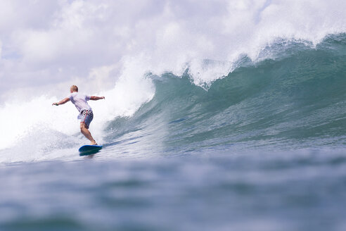 Indonesia, Bali, man surfing on a wave - KNTF00752