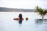 Indonesia, Lombok island, woman in infinty pool - KNTF00759