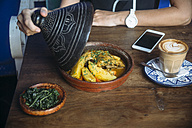 Indonesia, woman lifting serving dome of a dish in a cafe - KNTF00765