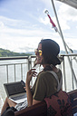 Indonesia, Lombok island, happy woman using laptop on ship deck - KNTF00768