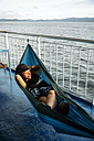 Indonesia, Lombok island, woman lying in hammock on ship deck - KNTF00771