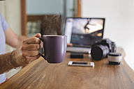 Photographer holding coffee cup at desk at home - KNTF00776