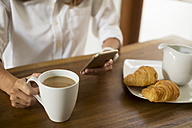 Woman at breakfast table using cell phone - KNTF00779