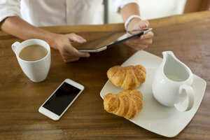 Woman at breakfast table using tablet - KNTF00782