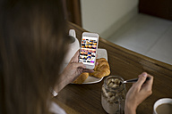 Woman at breakfast table looking at photos on cell phone - KNTF00785