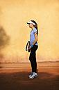 Teenage girl standing on tennis court - VABF01263