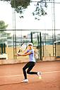 Teenage girl playing tennis on court - VABF01266