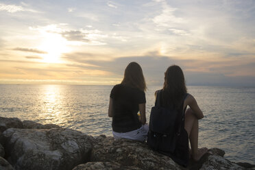 Indonesia, Bali, two women watching the sunset over the ocean - KNTF00792