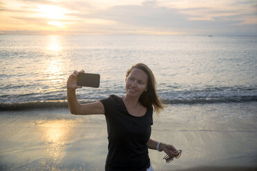 Indonesia, Bali, woman taking a selfie on the beach at sunset - KNTF00795