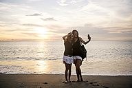 Indonesia, Bali, two women taking a selfie on the beach at sunset - KNTF00798