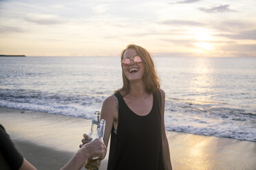 Indonesia, Bali, happy woman clinking beer bottle with friend on the beach at sunset - KNTF00801