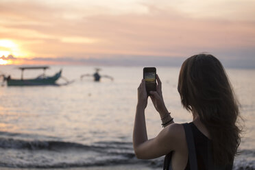 Indonesia, Bali, woman taking a picture of the sunset over the ocean - KNTF00804
