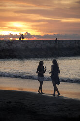 Indonesia, Bali, two women walking on the beach at sunset - KNTF00807