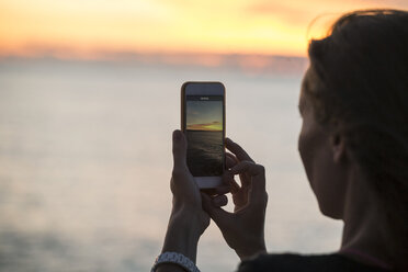 Indonesia, Bali, woman taking a picture of the sunset over the ocean - KNTF00810