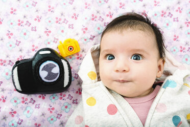 Portrait of baby girl lying on bed with two toy cameras - GEMF01526