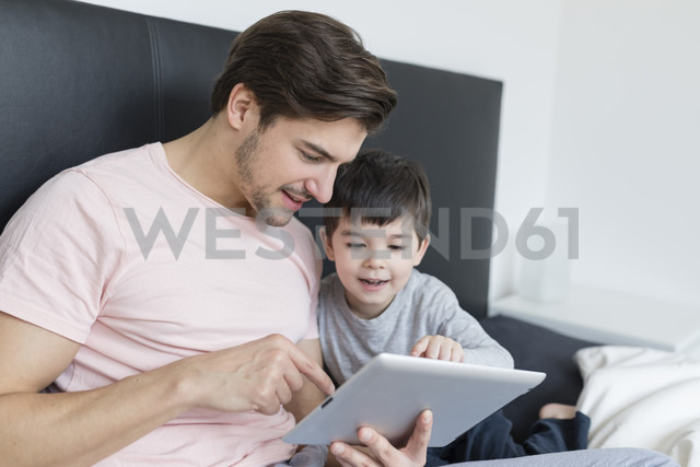 Father and son looking at tablet in bed - SHKF00739