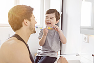 Happy father and son brushing teeth together in bathroom - SHKF00742