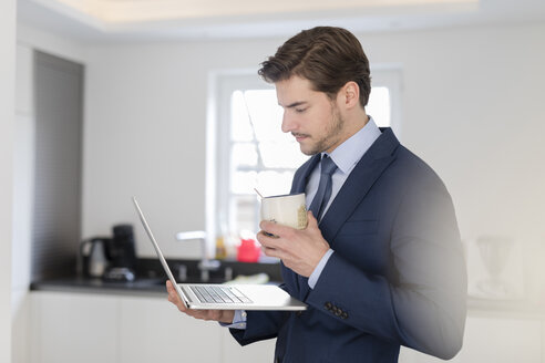 Businessman at home holding laptop and cup of coffee - SHKF00751
