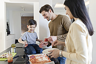 Family preparing pizza in kitchen together - SHKF00754