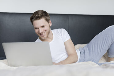 Smiling young man lying on bed using laptop - SHKF00757