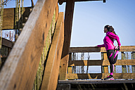Woman stretching on wooden bridge - SIPF01445