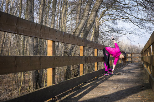 Woman stretching on wooden bridge in forest - SIPF01448