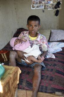 Madagascar, Fianarantsoa, Young boy holding baby on his lap - FLKF00798