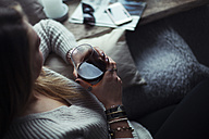 Young woman with glass of coffee relaxing on couch at home - NAF00061