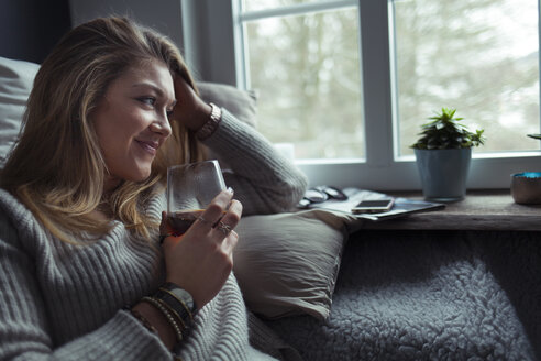 Smiling blond woman with glass of coffee relaxing on couch at home - NAF00064