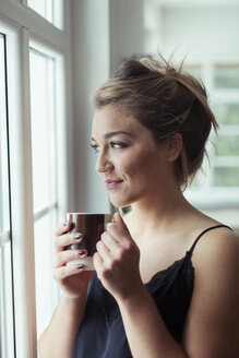 Portrait of smiling blond woman with glass of coffee looking through window - NAF00067