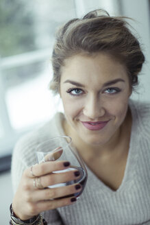 Portrait of smiling young woman with glass of coffee - NAF00082