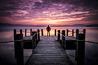 Italy, man standing on a jetty at sunset - SIPF01455