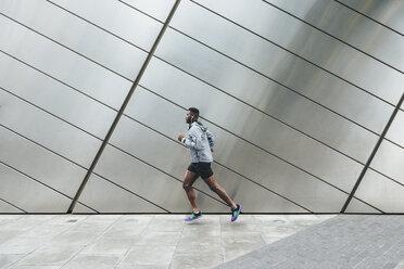 Young man running along building front - BOYF00670