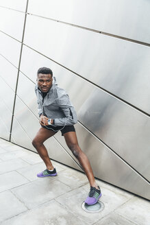 Athlete stretching at building front - BOYF00673